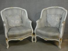 A pair of Louis XV style tub armchairs in damask upholstery and gilt and white painted frames on