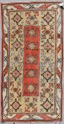 A Turkish Millas rug with repeating central flowerhead motif contained within broad stylised borders