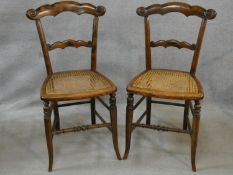 A pair of 19th century faux rosewood bedroom chairs with shaped and carved rail backs and caned