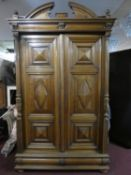 A 19th century French provincial chestnut armoire with fielded lozenge panelled doors enclosing