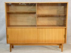 A 1960's vintage teak Beaver and Tapley Multi Width display cabinet on shaped splay supports. H.