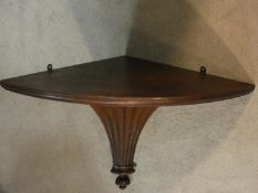 A 19th century mahogany corner wall bracket with reeded base. H.55 W.77 D.21cm