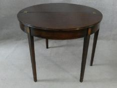 A Georgian mahogany and satinwood inlaid demi lune console tea table with foldover top and gateleg