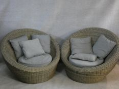 A pair of woven cane tub shaped conservatory chairs with fitted squab cushions. H.88cm