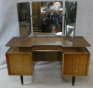 A mid century vintage teak G-Plan dressing table with adjustable triple mirrors above drawers on