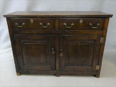 A Georgian country oak side cabinet with two frieze drawers above fielded panel doors with