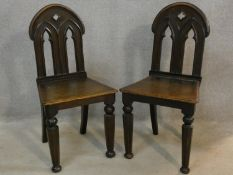 A pair of late 19th century oak hall chairs with Gothic carved and pierced backs above panel seats