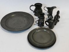 A collection of antique pewter items. Including plates, measures, pepper shaker, jug and tankards.