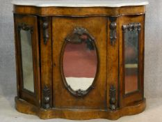 A Victorian burr walnut marble topped credenza with bowed and shaped top above carved and mirrored