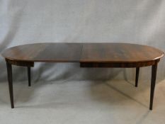 A Danish rosewood extending dining table with two extra leaves on square tapering supports. H.73 L.