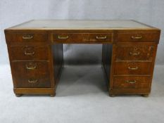 A mid century oak pedestal desk with inset leather top above an arrangement of nine drawers. H.