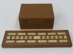 A 19th Century parquetry and bone inlaid cribbage board and pieces along with a wooden cased antique