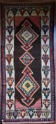 A Persian Kilim with repeating lozenge medallion on umber ground contained by plain spandrels and