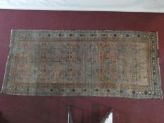 An Eastern rug with repeating gul motifs across the madder field within highly stylised foliate