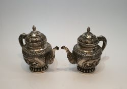 A pair of Chinese Tibetan white metal repousse design wine jugs. Decorated with animals, symbols and