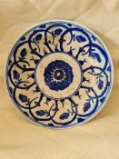 A 17th century Safavid Fritware blue and white ceramic plate, decorated with a stylized spiral