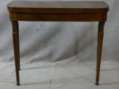 A 19th century mahogany and satinwood strung foldover top tea table on turned tapering supports. H.