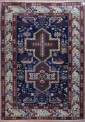 A fine Kazak style rug with double central medallions on indigo field with stylised animal and