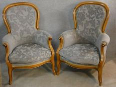 A pair of 19th century style beech framed armchairs in cut floral velour upholstery on carved