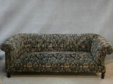A 19th century drop end Chesterfield sofa in floral buttoned upholstery on turned tapering supports.