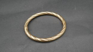 A vintage 9 ct yellow gold hollow twist bangle with secure loop clasp. Italian hallmarks, stamped