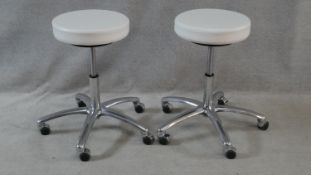 A pair of adjustable white vinyl stools on aluminium bases on casters. Makers label to the