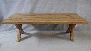 A contemporary hardwood refectory table on X frame supports. H.76 L.240 W.100cm