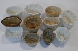 A collection of eleven vintage and antique ceramic/stoneware jelly moulds, some with floral and