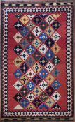 A Persian Kashkai Kilim with repeating diamond pattern on a blush field within geometric borders.