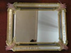 A Murano glass wall mirror with polychrome floral decoration and etched panels. H.70 W.87cm