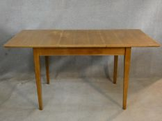 A mid century vintage teak dining table with extra leaf on square tapering supports. H.76 L.154 W.
