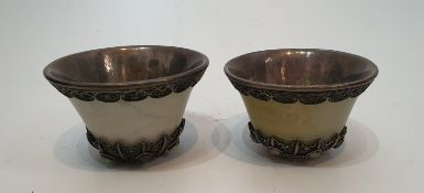 A pair of Chinese carved jade and white metal lined cups with white metal filigree wire work inset