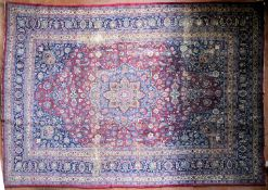 A Persian Mashad carpet with double central floral medallions on madder field within sapphire floral