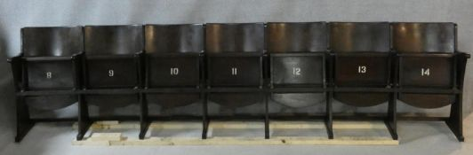 A row of seven vintage theatre seats with laminated plywood backs and seats and painted seat