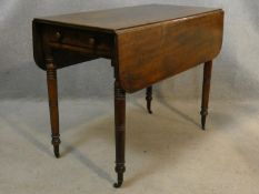 A 19th century mahogany Pembroke table on turned tapering supports terminating in brass cap casters.