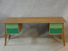 A vintage style teak writing desk with painted drawers to the kneehole section on splay supports.