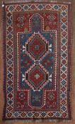 An antique Kazak rug with double lozenge medallion on indigo ground within a madder field