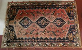 A Persian carpet with triple hooked central medallions with stylised bird motifs on the madder