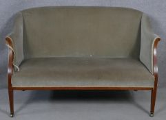An Edwardian mahogany and satinwood strung upholstered two seater tub shaped canape. H.85 W.130 D.