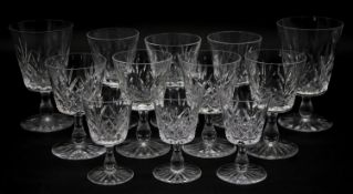 A collection of twelve glass sherry glasses with stylised foliate design and star cut bases. H.13cm