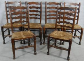 A set of six oak Lancashire ladderback dining chairs with woven rush seats on turned stretchered