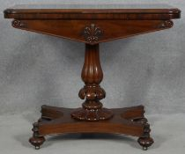 A William IV mahogany foldover top card table with baize lined surface on reeded bulbous pedestal