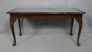 A Georgian style mahogany coffee table with inset plate glass top and tooled leather insert on
