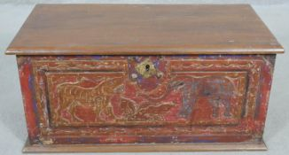 A small Eastern teak coffer with carved and painted animal decoration and twin metal carrying