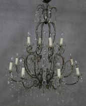 A metal framed sixteen branch chandelier with twelve light fittings in two tiers all with cut