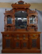 A late Victorian carved walnut mirror backed sideboard with shaped bevelled plates and turned