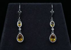 A pair of 14 carat and 9 carat white gold articulated citrine and diamond drop earrings. Each