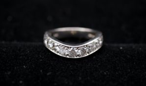 A platinum and diamond curved half eternity ring. Set with eleven round brilliant cut diamonds