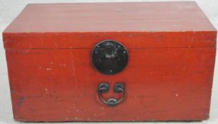 A vintage Chinese lacquered trunk with metal clasp and twin carrying handles. H.38 W.72 D.40cm