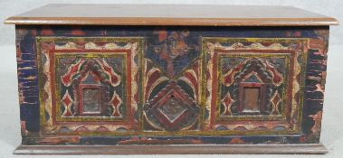 A small Eastern teak coffer with carved and painted floral decoration and twin metal carrying